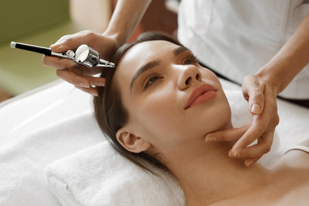 spa therapy: Facial Beauty Treatment. Closeup Of Beautiful Woman Getting Oxygen Epidermal Peeling At Cosmetic Beauty Spa Salon. Girl Enjoying  Skin Rejuvenation Therapy At Cosmetology Center. High Resolution Image