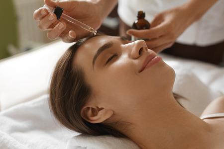 Péče o pleť obličeje. Detailní krásné usmívající se žena obdrží Serum Oil zacházení v salonu krásy. Kosmetička použití kosmetického sérum na dívčí tvář At Kosmetika Center. Vysoké rozlišení obrazu