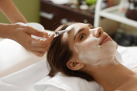 cosmetologist: Skin Care. Beautiful Healthy Woman Getting Cosmetic Mask At Spa Salon. Closeup Of Cosmetologist Hands Applying Mask With Brush On Females Face. Facial Beauty Treatment Concept. High Resolution Image