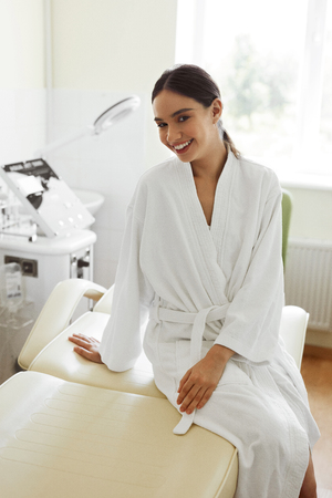 Beautiful Woman In Day Spa Salon. Healthy Happy Smiling Girl In Bathrobe Sitting On Massage Table In Cosmetology Room At Beauty Spa Centre. Pampering And Body Care Concept. High Resolution Image