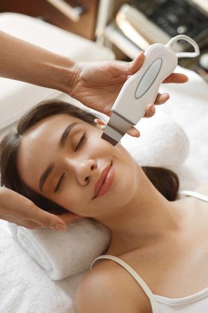 Cuidado de la piel de la cara. Mujer hermosa que recibe ultrasonido cavitación Peeling en salón de belleza. Muchacha que consigue ultrasónico Tratamiento facial, procedimiento de limpieza de la piel en cosmetología Center. Imagen de alta resolución