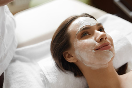 Face Skin Care. Closeup Of Beautiful Healthy Smiling Woman With White Cosmetic Mask On Her Face Relaxing And Enjoying Facial Beauty Treatment At Day Spa Salon Indoors. High Resolution Image