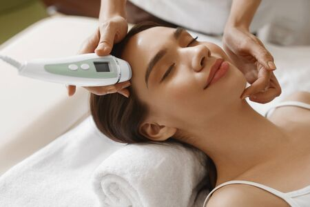 cosmetologist: Skin Care. Beautiful Healthy Woman Getting Her Skin Analized By Cosmetologist, Using Skin Analyzer ( Professional Beauty Equipment ) For Face Skin Analysis At Cosmetology Center. High Resolution Image