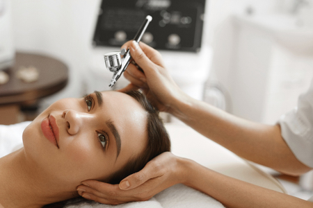 medical treatment: Facial Skin Care. Closeup Of Beautiful Woman Receiving Face Oxygen Peeling At Cosmetology Center. Girl Enjoying Skin Rejuvenation Procedure. Beauty Treatment Concept. High Resolution Image Stock Photo