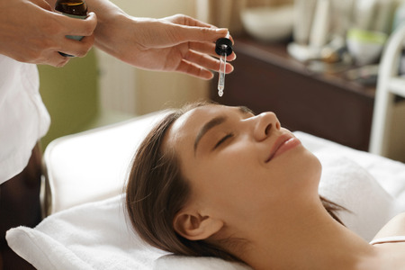 cosmetologist: Face Skin Care. Closeup Of Beautiful Smiling Woman Receiving Serum Oil Treatment In Beauty Salon. Cosmetologist Applying Cosmetic Serum On Girls Face At Cosmetology Center. High Resolution Image Stock Photo