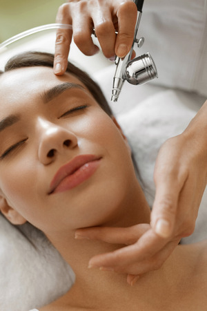 Facial Skin Care. Closeup Of Beautiful Woman Receiving Face Oxygen Peeling At Cosmetology Center. Girl Enjoying Skin Rejuvenation Procedure. Beauty Treatment Concept. High Resolution Image Stock Photo