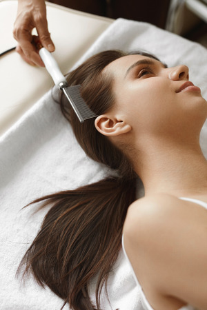 cosmetologist: Hair Care. Closeup Of Beautiful Woman Receiving Medical Hair Beauty Treatment At Cosmetology Center. Cosmetologist Brushing Girls Healthy Hair With Comb Brush For Keratin Supply. High Resolution