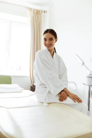 massage table: Beautiful Woman In Day Spa Salon. Healthy Happy Smiling Girl In Bathrobe Sitting On Massage Table In Cosmetology Room At Beauty Spa Centre. Pampering And Body Care Concept. High Resolution Image