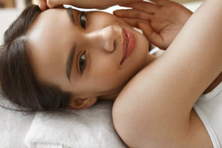 Beauty Woman Face. Closeup Portrait Of Beautiful Smiling Young Female With Natural Makeup, Healthy Fresh Skin Lying On Bed. Happy Attractive Girl Relaxing. Skin Care Concept. High Resolution Image