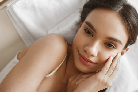 natural face: Beauty Woman Face. Closeup Portrait Of Beautiful Smiling Young Female With Natural Makeup, Healthy Fresh Skin Lying On Bed. Happy Attractive Girl Relaxing. Skin Care Concept. High Resolution Image