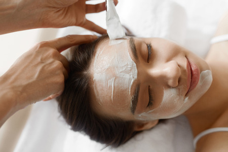 face mask: Facial Beauty Treatment. Closeup Of Beautiful Smiling Woman Getting Mask At Spa Salon. Cosmetologist Applying Cosmetic Mask With Brush On Female Face Indoors. Skin Care Concept. High Resolution Image