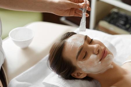 Tratamiento de belleza facial. Detalle de hermosa mujer sonriente que consigue la máscara en el salón del balneario. La aplicación de cosmetólogo Máscara Cosmética con el cepillo en cara femenina Interior. Piel Care Concept. Imagen de alta resolución