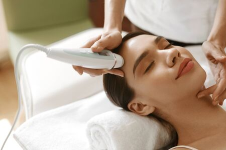 medical center: Skin Care. Beautiful Healthy Woman Getting Her Skin Analized By Cosmetologist, Using Skin Analyzer ( Professional Beauty Equipment ) For Face Skin Analysis At Cosmetology Center. High Resolution Image