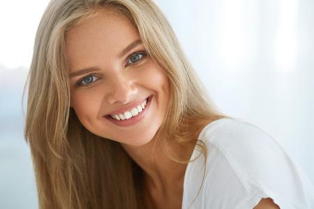 美しい女性の笑顔します。完璧な笑顔、白い歯、ブロンドの髪と新鮮な顔が屋内で笑顔と魅力的な幸せな健康的な女の子の肖像画。美容と医療の概