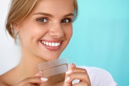 Teeth Whitening. Closeup Portrait Of Beautiful Happy Smiling Young Woman With Perfect Smile, Healthy White Teeth Holding Teeth Whitening Strip. Dental Beauty And Health Concept. High Resolution Image