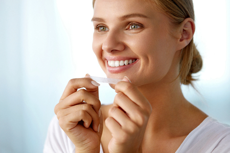 a tooth are beautiful: White Smile. Beautiful Smiling Woman With Healthy White Teeth Applying Teeth Whitening Strip. Portrait Of Happy Girl Using Dental Whitener. Dental Beauty, Tooth Care Concept. High Resolution Image