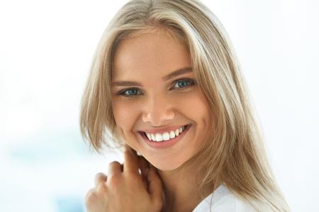 Piękna kobieta uśmiecha. Portret atrakcyjne Szczęśliwa zdrowa dziewczyna Z Perfect Smile, białe zęby, blond włosy i Świeże uśmiechnięta twarz w pomieszczeniach zamkniętych. Koncepcja zdrowia i urody. Wysoka rozdzielczość obrazu