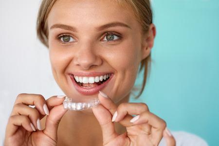 Sbiancamento dei denti. Bella donna sorridente con sorriso bianco, denti dritti Uso Teeth Whitening vassoio. Girl Holding invisibile parentesi graffe, Denti Trainer. Dental Concept trattamento. Immagini ad alta risoluzione Archivio Fotografico
