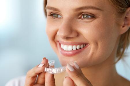 화이트 미소. 건강 스트레이트 하얀 치아는 치과 표백제를 사용하여 치아 미백 트레이, 소녀를 들고 아름 다운 미소 여자의 초상화. 치과 미용 치료 개