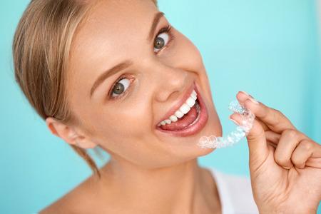 White Smile. Portrait de belle femme souriante avec des dents blanches droites holding de blanchiment des dents Plateau, Fille Utilisation dentaire Whitener. Dental Beauty Concept traitement. Image à haute résolution Banque d'images