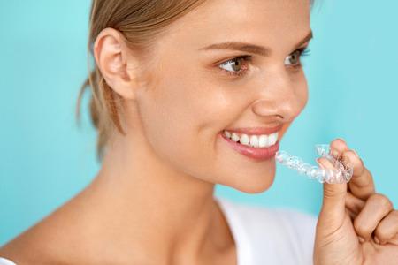ortodoncia: Ortodoncia. Detalle de la hermosa mujer sonriente feliz con la sonrisa blanca, recta dientes que blanquea la celebración de la bandeja, aparatos invisibles, Dientes Trainer. El tratamiento dental, concepto de la salud. Imagen de alta resolución