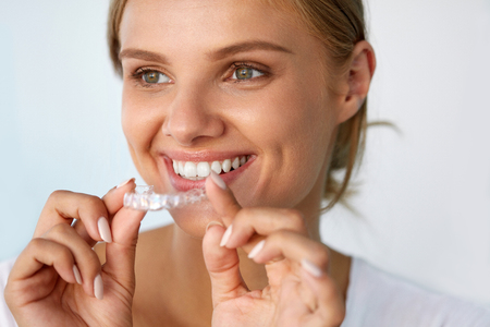 Teeth Whitening. Beautiful Smiling Woman With White Smile, Straight Teeth Using Teeth Whitening Tray. Girl Holding Invisible Braces, Teeth Trainer. Dental Treatment Concept. High Resolution Image Foto de archivo
