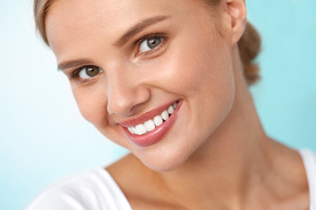 Beautiful Smile. Closeup Portrait Of Beautiful Happy Young Woman With Perfect White Teeth, Fresh Beauty Face And Healthy Soft Skin Smiling. Woman's Health, Skin Care Concept. High Resolution Image