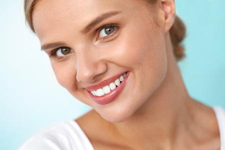 Mooie glimlach. Close-up portret van mooie gelukkige jonge vrouw met perfecte witte tanden, Verse Gezicht van de Schoonheid en gezonde Soft Skin Glimlachen. Woman's Health, Skin Care Concept. Hoge Resolutie Afbeelding