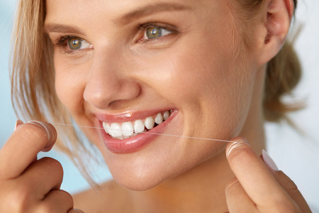 a tooth are beautiful: Dental Health. Closeup Portrait Of Beautiful Happy Smiling Young Woman With Perfect Smile Cleaning Healthy White Teeth, Flossing Using Floss. Tooth Care, Oral Hygiene Concept. High Resolution Image