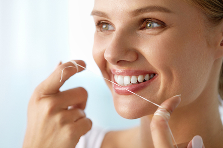 dientes sanos: Los dientes Care. Detalle de la hermosa mujer sonriente feliz con sonrisa perfecta a limpiarse los dientes blancos sanos, uso de hilo dental uso de hilo. (Boca) Higiene oral, concepto de la salud dental. Imagen de alta resolución