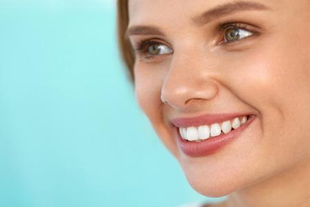 美容女性の顔。完璧な笑顔と白い歯で美しい幸せな女の子のポートレート、クローズ アップ。新鮮な柔らかい肌を笑顔で明るく健康的な女性。健康