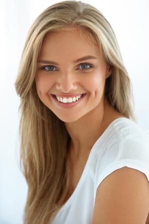 Retrato de mujer de belleza. Primer plano de hermosa niña feliz con una sonrisa perfecta, dientes blancos sonriendo a la cámara. Atractiva mujer joven sana con maquillaje de cara natural fresco en el interior. Imagen de alta resolución
