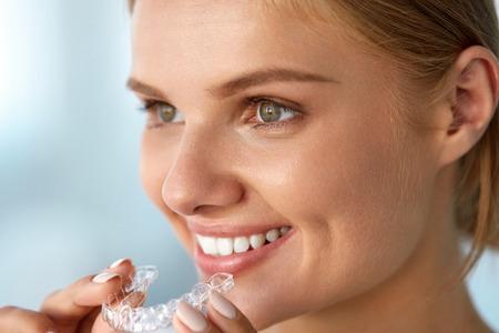 Orthodontie. Close-up Van Mooie gelukkig lachende vrouw met witte glimlach, rechte tanden Holding Whitening Tray, onzichtbare beugels, tanden Trainer. Tandheelkundige behandeling, Gezondheid Concept. Hoge Resolutie Afbeelding