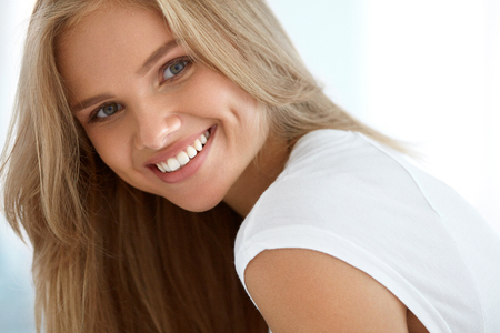 아름다움 여자의 초상화입니다. 완벽한 미소로 아름다운 행복한 여자의 근접 촬영, 화이트 치아는 미소를 카메라. 실내 신선한 자연 얼굴 메이크업으