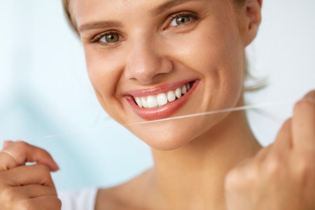 a tooth are beautiful: Dental Hygiene. Closeup Of Beautiful Happy Smiling Woman With Beauty Face And Perfect Smile Cleaning, Flossing Healthy White Teeth Using Floss. Oral Health, Tooth Care Concept. High Resolution Image