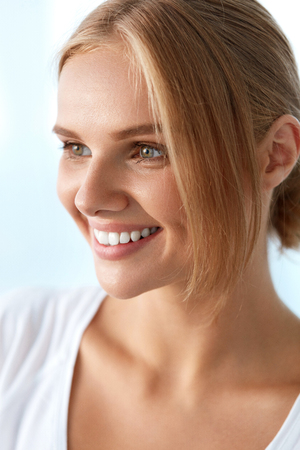 fresh face: Beauty Woman Portrait. Beautiful Happy Smiling Girl With Perfect White Smile, Blonde Hair And Fresh Face Touching Her Healthy Soft Skin. Womans Health, Skin Care Concept. High Resolution Image