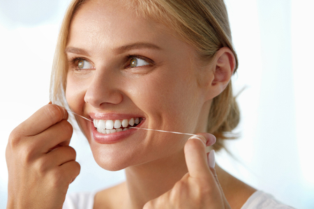 flossing: Teeth Care. Closeup Of Beautiful Happy Smiling Woman With Perfect Smile Cleaning Her Healthy White Teeth, Flossing Using Floss. ( Mouth ) Oral Hygiene, Dental Health Concept. High Resolution Image