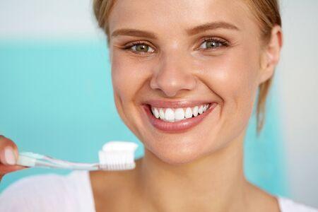 Lavando los dientes. Primer plano de la mujer feliz hermosa con sonrisa perfecta, dientes blancos sanos, frescos rostro la celebración de cepillo de dientes con pasta de dientes. Higiene oral, Concepto de salud dental. Imagen de alta resolución