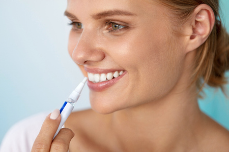 a tooth are beautiful: Healthy White Teeth. Closeup Portrait Of Beautiful Happy Smiling Woman With Perfect White Smile Holding Teeth Whitening Pen. Dental Beauty And Health, Tooth Care Concept. High Resolution Image