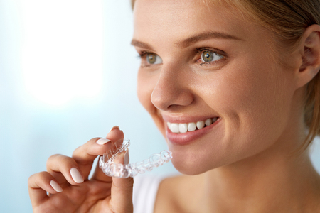 invisible: Orthodontics. Closeup Of Beautiful Happy Smiling Woman With White Smile, Straight Teeth Holding Whitening Tray, Invisible Braces, Teeth Trainer. Dental Treatment, Health Concept. High Resolution Image