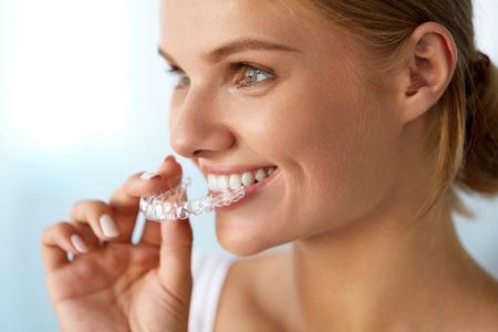 Kieferorthopädie. Nahaufnahme der schönen glücklich lächelnde Frau mit weißen Lächeln, gerade Zähne Halten Whitening Tray, Unsichtbare Zahnspangen, Zähne Trainer. Zahnbehandlung, Gesundheits-Konzept. Hohe Auflösung Bild