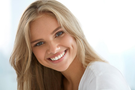 Beauty Woman Portrait. Closeup Of Beautiful Happy Girl With Perfect Smile, White Teeth Smiling At Camera. Attractive Healthy Young Female With Fresh Natural Face Makeup Indoors. High Resolution Image Stock Photo