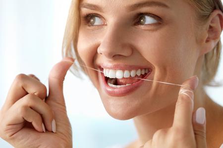 Zahnpflege. Nahaufnahme der schönen glücklich lächelnde Frau mit Perfect Smile ihre gesunde weiße Zähne reinigen, Flossing Seide. (Mund) Mundhygiene, Zahnpflege-Konzept. Hohe Auflösung Bild