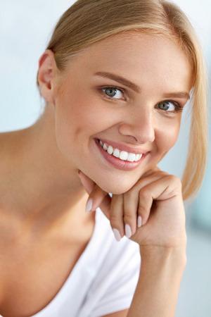 美しい女性の肖像画。完璧な白い笑顔、ブロンドの髪と彼女の健康的な柔らかい肌に触れて新鮮な顔と美しい幸せな笑顔の女の子。女性の健康、肌