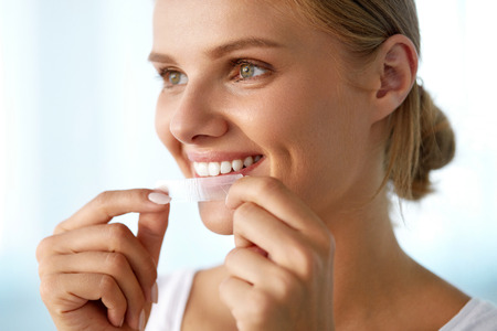 a tooth are beautiful: Healthy White Teeth. Beautiful Smiling Girl Holding Teeth Whitening Strip. Happy Young Woman With Perfect White Smile Using Dental Whitener. Dental Beauty, Tooth Care Concept. High Resolution Image