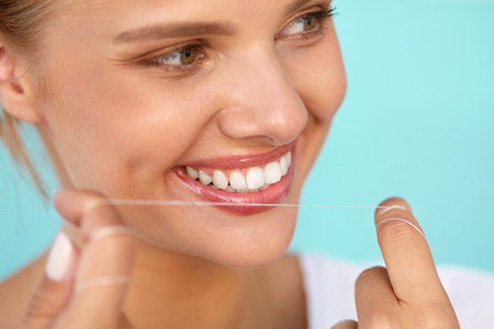 flossing: Dental Hygiene. Closeup Of Beautiful Happy Smiling Woman With Beauty Face And Perfect Smile Cleaning, Flossing Healthy White Teeth Using Floss. Oral Health, Tooth Care Concept. High Resolution Image