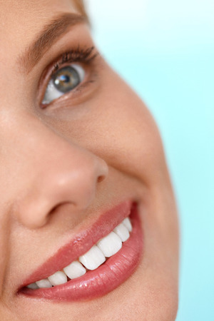 balsam: Beautiful Smile. Closeup Of Beautiful Happy Smiling Woman With White Teeth And Fresh Face. Beauty Girl With Cosmetic Lip Balm On Her Full Lips. Dental Health, Lip Care Concept. High Resolution Image
