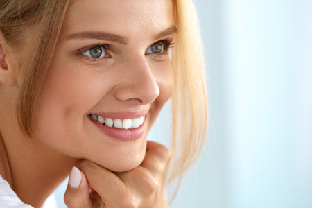Beauty Woman Portrait. Beautiful Happy Smiling Girl With Perfect White Smile, Blonde Hair And Fresh Face Touching Her Healthy Soft Skin. Woman's Health, Skin Care Concept. High Resolution Image
