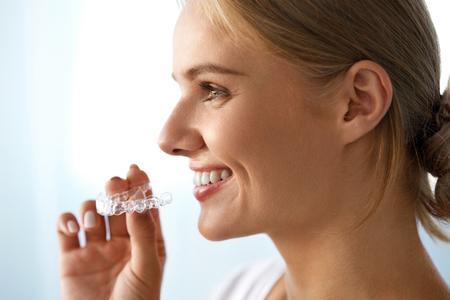 appareil dentaire: Orthodontie. Gros plan de Belle Bonne femme souriante avec sourire blanc, dents droites Tenir blanchissant Plateau, Bretelles invisibles, Teeth Trainer. Soins dentaires, Concept Santé. Image à haute résolution