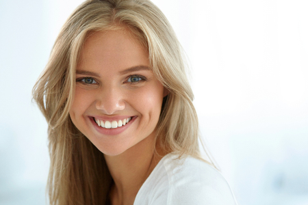 Beauty Woman Portrait. Closeup Of Beautiful Happy Girl With Perfect Smile, White Teeth Smiling At Camera. Attractive Healthy Young Female With Fresh Natural Face Makeup Indoors. High Resolution Image